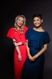 Zwei schöne Mädchen in den Abendkleidern lächelnd über grauem Hintergrund Lizenzfreie Stockbilder
