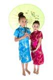 Zwei schöne Mädchen, die Asiatskleider unter Regenschirm tragen Lizenzfreie Stockbilder