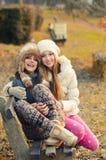 Zwei schöne Mädchen, die auf der Bank im Freien auf sonnigem Herbst sitzen Lizenzfreies Stockbild