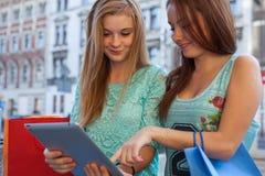 Zwei schöne Mädchen, die auf einer Bank mit Tabletten-PC sitzen Lizenzfreie Stockfotografie