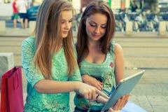 Zwei schöne Mädchen, die auf einer Bank mit Tabletten-PC sitzen Lizenzfreie Stockbilder
