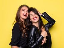 Zwei schöne Mädchen, die auf gelbem Hintergrund umarmen lizenzfreie stockbilder
