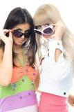 Zwei schöne Mädchen, die auf Sonnegläsern versuchen Stockfotos