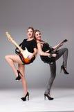 Zwei schöne Mädchen, die Gitarren spielen Lizenzfreies Stockbild