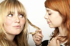 Zwei schöne Mädchen, die Haar betrachten Stockfotos