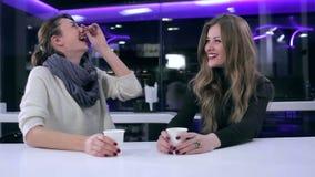 Zwei schöne Mädchen, die im Café sprechen stock video