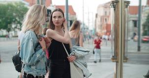 Zwei schöne Mädchen, die Kleidung in einem Shopfenster betrachten Lizenzfreie Stockbilder