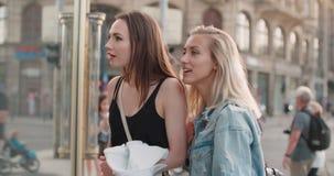 Zwei schöne Mädchen, die Kleidung in einem Shopfenster betrachten Stockbilder