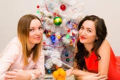 Zwei schöne Mädchen, die nahe bei einem Weihnachtsbaum liegen Stockfotos