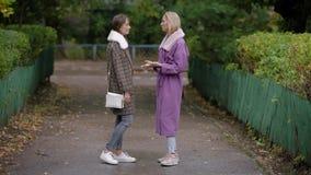 Zwei schöne Mädchen in einem Mantel Herbst, die schöne Zeit für das Gehen durch die Stadtstraßen stock footage