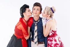Zwei schöne Mädchen in einem Weinlesekleid küssen stilvollen Mann Lizenzfreies Stockfoto