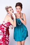 Zwei schöne Mädchen in einer Weinlese kleiden das Erzählen von Geschichten lizenzfreie stockfotos