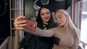 Zwei schöne Mädchen machen selfie auf Smartphone im Restaurant stock video footage
