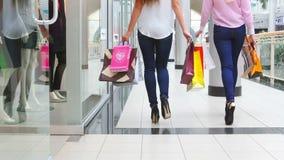 Zwei schöne Mädchen mit den Einkaufstaschen herausgekommen stock video footage