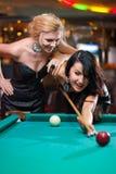 Zwei schöne Mädchen spielen Billiarde lizenzfreie stockfotografie