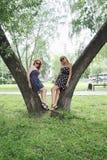 Zwei schöne Mädchen stehen nahe Bäume Stockfotos