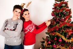 Zwei schöne Mädchenhaltungen und verzieren großen Weihnachtsbaum stockbilder