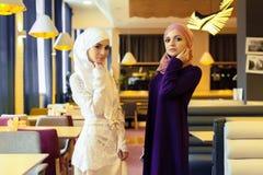 Zwei schöne moslemische Frauen in der modernen orientalischen Kleidung stockfotos