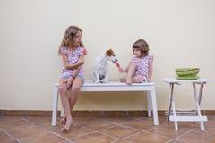 Zwei schöne Schwesterkinder, die eine WassermelonenEiscreme essen Familienliebe und Lebensstilfreien lizenzfreie stockbilder