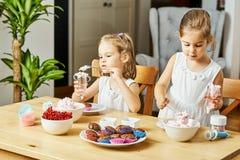 Zwei schöne Schwestern in den weißen Kleidern verzieren und essen köstliche kleine Kuchen stockfotografie