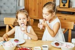Zwei schöne Schwestern in den weißen Kleidern verzieren und essen köstliche kleine Kuchen lizenzfreies stockbild