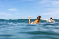 Zwei schöne sportliche Mädchen, die in den Ozean surfen stockbilder