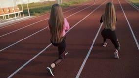 Zwei schöne Sportmädchen mit einer guten Zahl auf dem Stadionszug Mädchen bilden bei Sonnenuntergang aus stock video