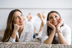 Zwei schöne sprechende und beim Lügen lächelnde Mädchen auf einem Bett Stockbilder