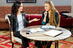 Zwei schöne Studentinnen werden für das Seminar am Café vorbereitet lizenzfreies stockfoto