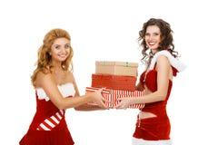 Zwei schöne Weihnachtsmädchen lokalisierten den weißen Hintergrund, der Geschenke hält Lizenzfreie Stockfotos