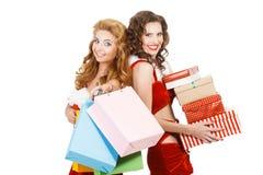 Zwei schöne Weihnachtsmädchen lokalisierten den weißen Hintergrund, der Geschenke und Pakete hält Stockfotos