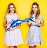 Zwei schönes Mädchenhändchenhalten der netten Freundinnen auf aufblasbarem Delphin des Spielzeugs innen stockfotografie