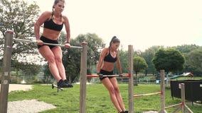 Zwei Schönheiten, die verschiedene Körpergewichtübungen an der horizontalen Stange tun stock footage