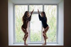 Zwei Schönheiten, die Yoga asana Adler tun, werfen auf Fensterbrett auf Stockbild