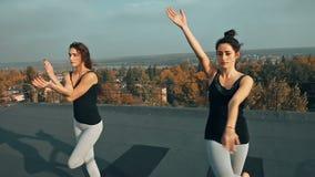 Zwei Schönheiten, die Yoga asana auf dem Dach, draußen am Morgen üben stock footage