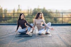 Zwei Schönheiten, die Yoga asana virabhadrasana auf dem Dach tun Lizenzfreies Stockfoto