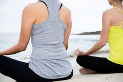 Zwei Schönheiten, die Yoga am Strand üben Stockfoto