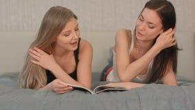 Zwei Schönheiten, die Zeitschrift an lesen stock footage