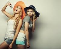 Zwei Schönheitsmädchen mit einem Mikrofon Lizenzfreies Stockbild