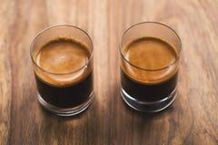Zwei Schüsse Espresso auf hölzerner Tabelle stockfotografie