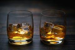 Zwei Schüsse Whisky mit Eis auf einem schwarzen Holztisch stockbilder