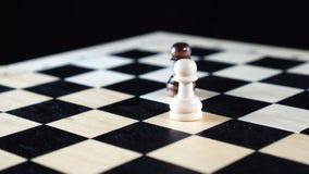 Zwei Schachschwarzweiss-Pfand, die auf ein Brett sich drehen stock video footage