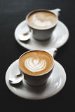 Zwei Schalen Cappuccino auf schwarzer Tabelle Stockfotografie