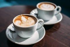 Zwei Schalen Cappuccino mit Lattekunst auf Holztisch stockfotos