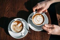 Zwei Schalen Cappuccino mit Lattekunst auf Holztisch in den Händen des Mannes lizenzfreie stockbilder