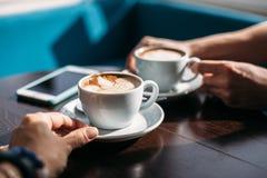 Zwei Schalen Cappuccino mit Lattekunst auf Holztisch in den Händen des Mannes und der Frau lizenzfreie stockbilder