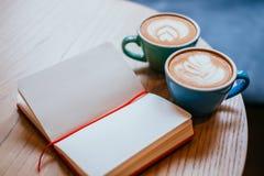 Zwei Schalen Cappuccino mit Notizbuch lizenzfreies stockbild