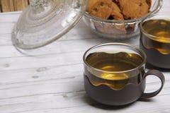 Zwei Schalen des grünen Tees und der Schüssel choco Chipplätzchen stockbilder