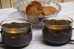 Zwei Schalen des grünen Tees und der Schüssel choco Chipplätzchen lizenzfreie stockfotos