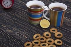 Zwei Schalen für Tee mit wohlriechenden Bageln auf hölzernem Hintergrund Lizenzfreies Stockfoto